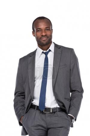 smiling african american businessman in suit with hands in pockets  isolated on white