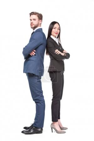 side view of multicultural business colleagues with arms crossed standing back to back isolated on white