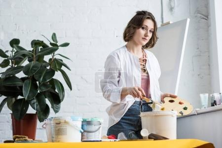 Young inspired girl holding palette and looking at camera in light studio