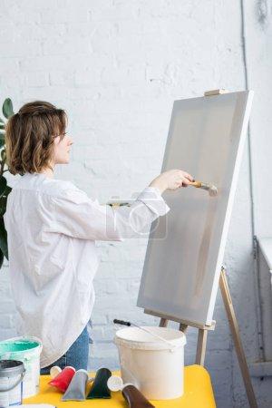 Joven chica creativa aplicando imprimación artística en estudio de luz