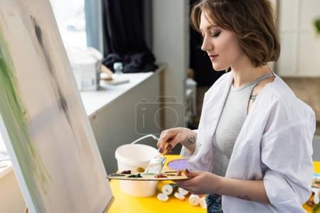 Photo pour Jeune fille inspirée mélange de peinture en studio lumière - image libre de droit