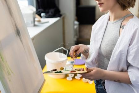 Young artistic girl holding palette and brush in light studio