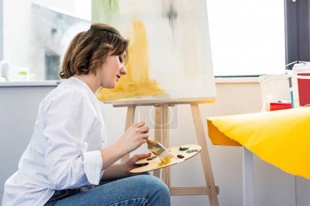 junges inspiriertes Mädchen arbeitet mit Palette im Lichtstudio