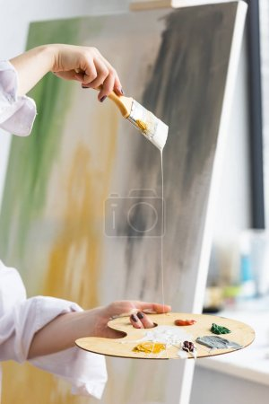 Close-up view of creative girl holding brush and palette in light studio