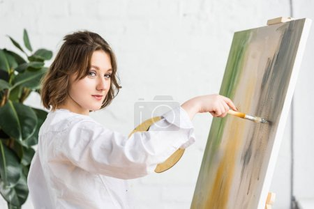 Young inspired girl working by easel in light studio
