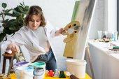 """Постер, картина, фотообои """"Молодая девушка художественных, выбирая краску в свете студии"""""""