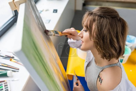 Photo for Young inspired girl painting by easel in light studio - Royalty Free Image