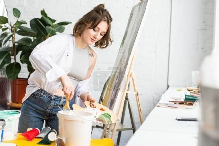 Photo pour Jeune fille inspirée plonge un pinceau dans la peinture en studio léger - image libre de droit