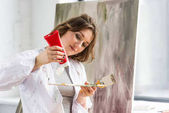 """Постер, картина, фотообои """"Молодая девушка творческие, сжимая краска трубки в свете студии"""""""