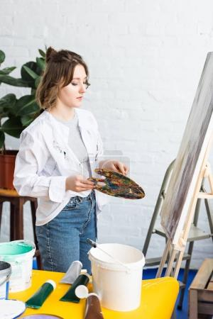 Young artistic girl with palette in light studio