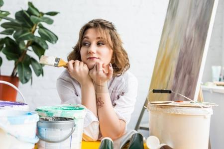 Young inspired girl dreaming with brushes in hands in light studio