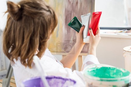 Young inspired girl choosing paint tube in light studio