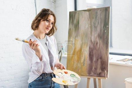 Photo pour Jeune fille inspirée rêver avec palette en main en studio lumineux - image libre de droit