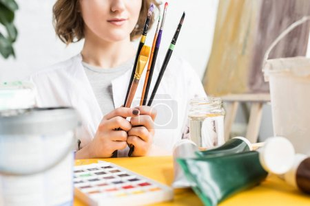 Photo for Close-up view of young artistic girl with brushes in hands in light studio - Royalty Free Image