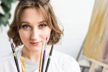 Photo pour Jeune fille inspirée regardant la caméra avec des brosses dans les mains en studio de lumière - image libre de droit