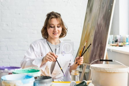 Young inspired girl with brushes in hands in light studio