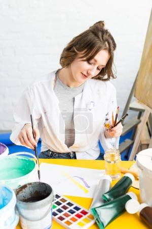 Young artistic girl making paint samples in light studio