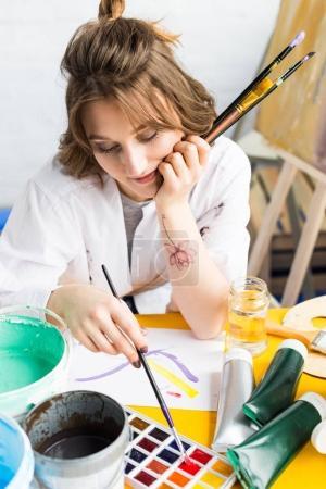 Young creative girl feeling bored in light studio