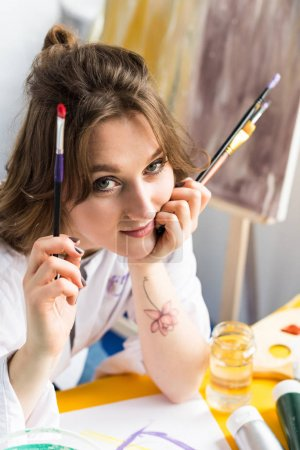Young inspired girl holding brushes and looking at camera in light studio
