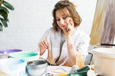 Young artistic girl painting by table in light studio