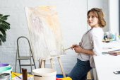 Young artistic girl standing by easel with brush in light studio