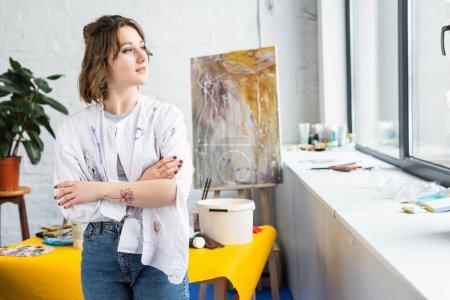 Young artistic girl looking in window in light studio