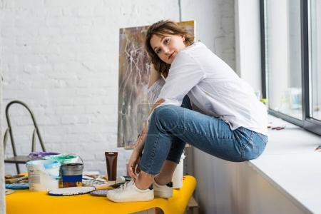 Young girl sitting on windowsill in light studio