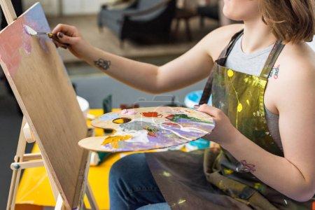 Young inspired girl applying primer on canvas in light studio
