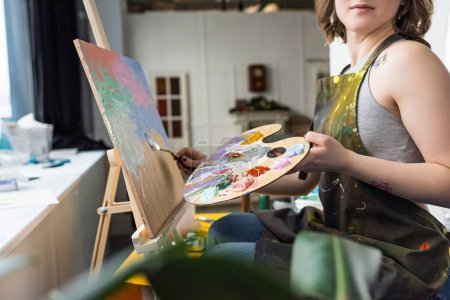 Close-up view of young inspired girl painting in light studio