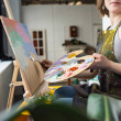 Close-up view of young inspired girl painting in l...