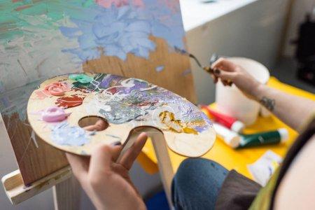 Photo pour Vue rapprochée de la fille avec la palette dans les mains dans les studio lumineux - image libre de droit