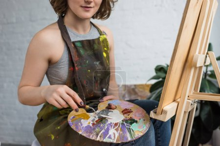 Close-up view of young creative girl with painting knife in light studio