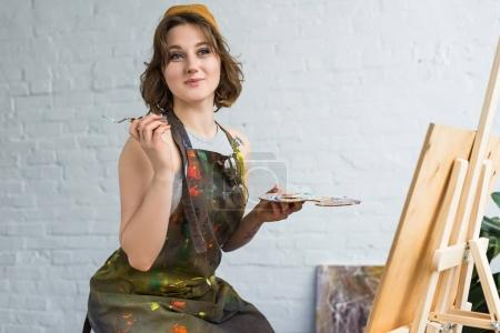 Young inspired girl working with painting knife by easel in light studio