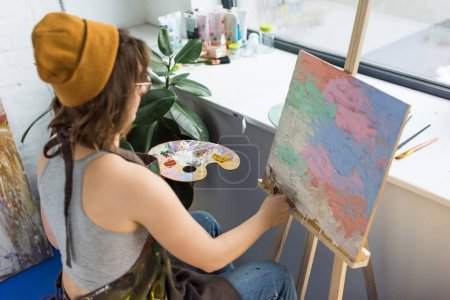 Young artistic girl working with painting knife and canvas in light studio