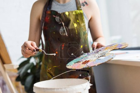 Close-up view of young inspired girl working with painting knife and palette in light studio