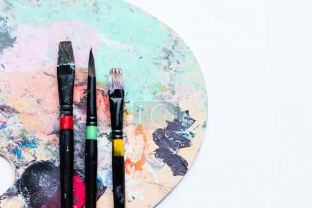 Photo for Artistic brushes on palette covered with colorful paint spots - Royalty Free Image