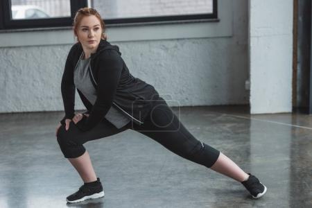 Overweight girl stretching legs in gym