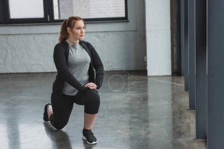 Obese girl performing stretching exercises in gym