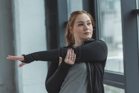 Overweight girl stretching arms in gym