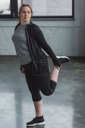 Obese girl stretching her leg in gym