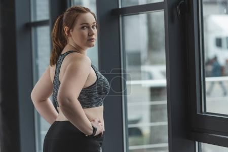 Close-up view of overweight girl standing by window in gym