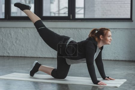 Overweight girl performing exercise in gym