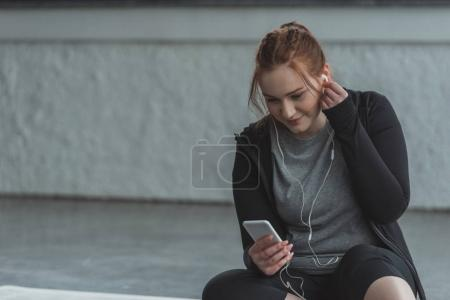 Obese girl listening to music on smartphone in gym