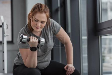 Curvy girl lifting dumbbell in gym
