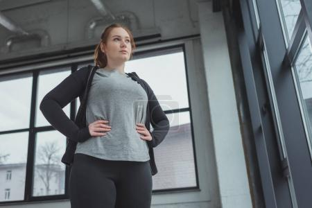 Overweight girl in sportswear standing by window in gym