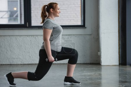 Photo for Obese girl performing lunges with dumbbell in gym - Royalty Free Image
