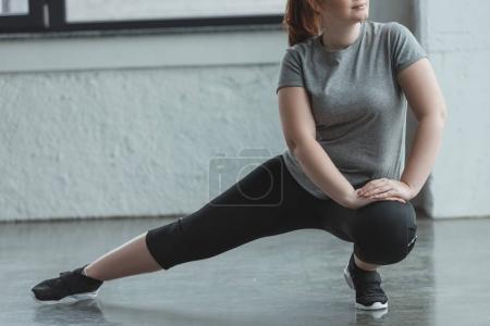 Photo pour Surpoids fille étirant les jambes dans la salle de gym - image libre de droit