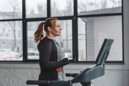Overweight girl running on treadmill in sports center