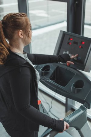 Curvy girl adjusting treadmill in gym