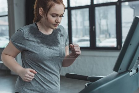 Photo for Overweight girl running on treadmill in gym - Royalty Free Image